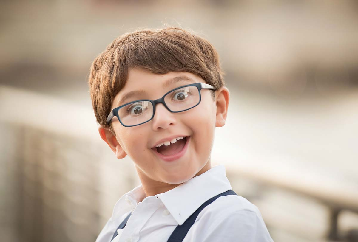 Young boy in glasses making silly faces at the camera in this beautiful child photo