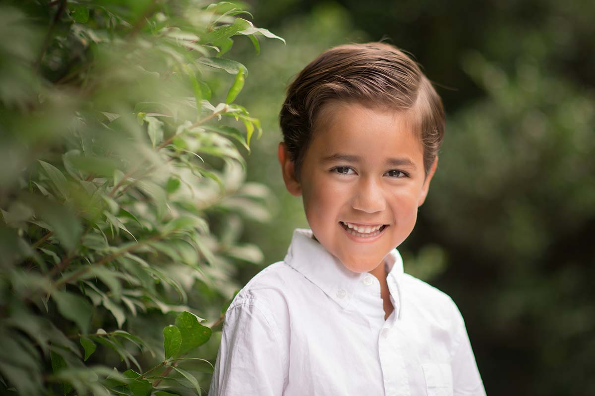 Botanical Gardens in Westchester Co, NY are the setting for this beautiful photo of a young boy in a white shirt smiling for the camera
