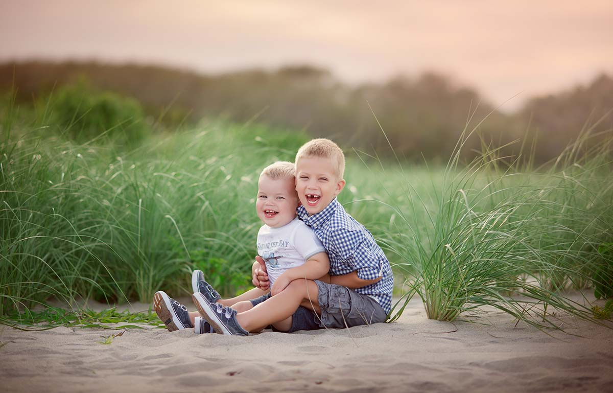 Two cute brothers with blonde hair hugging on a grassy beach near Norwalk, CT.