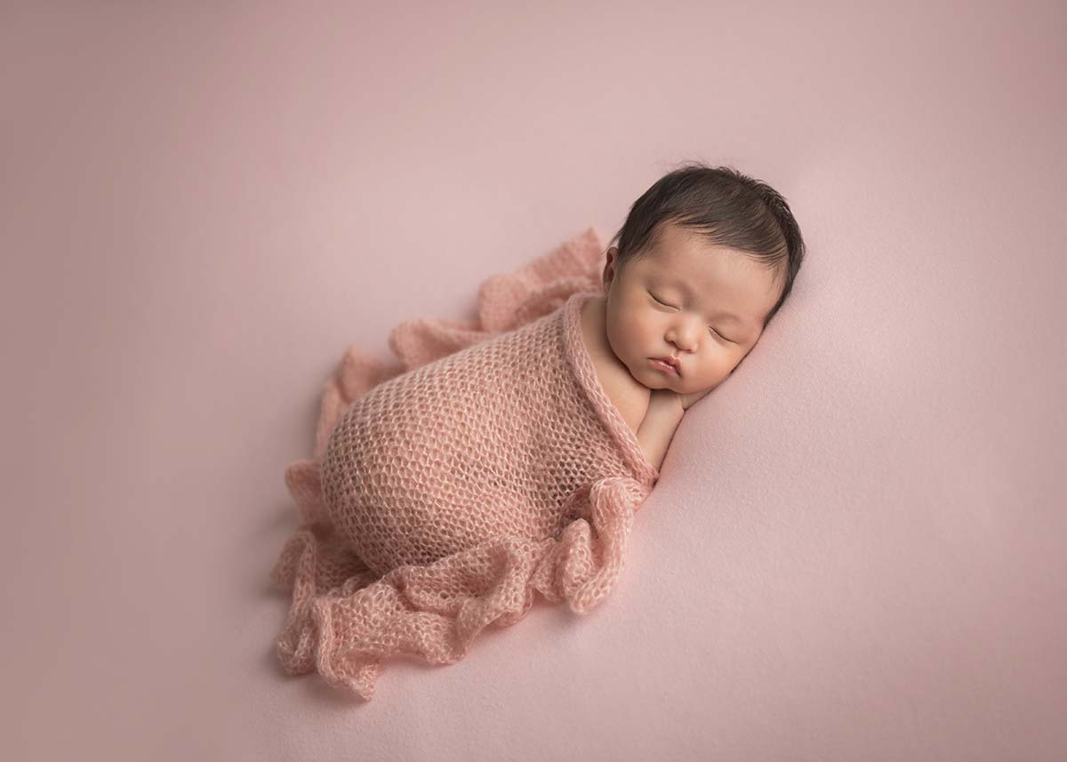 Baby girl in a pink wrap sleeping while posing for a newborn photo