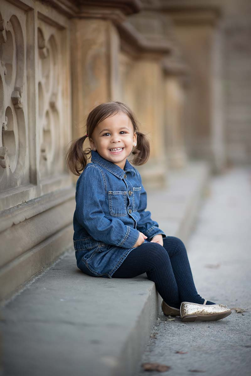 Cute baby girl sitting on a bench at a park and smiling