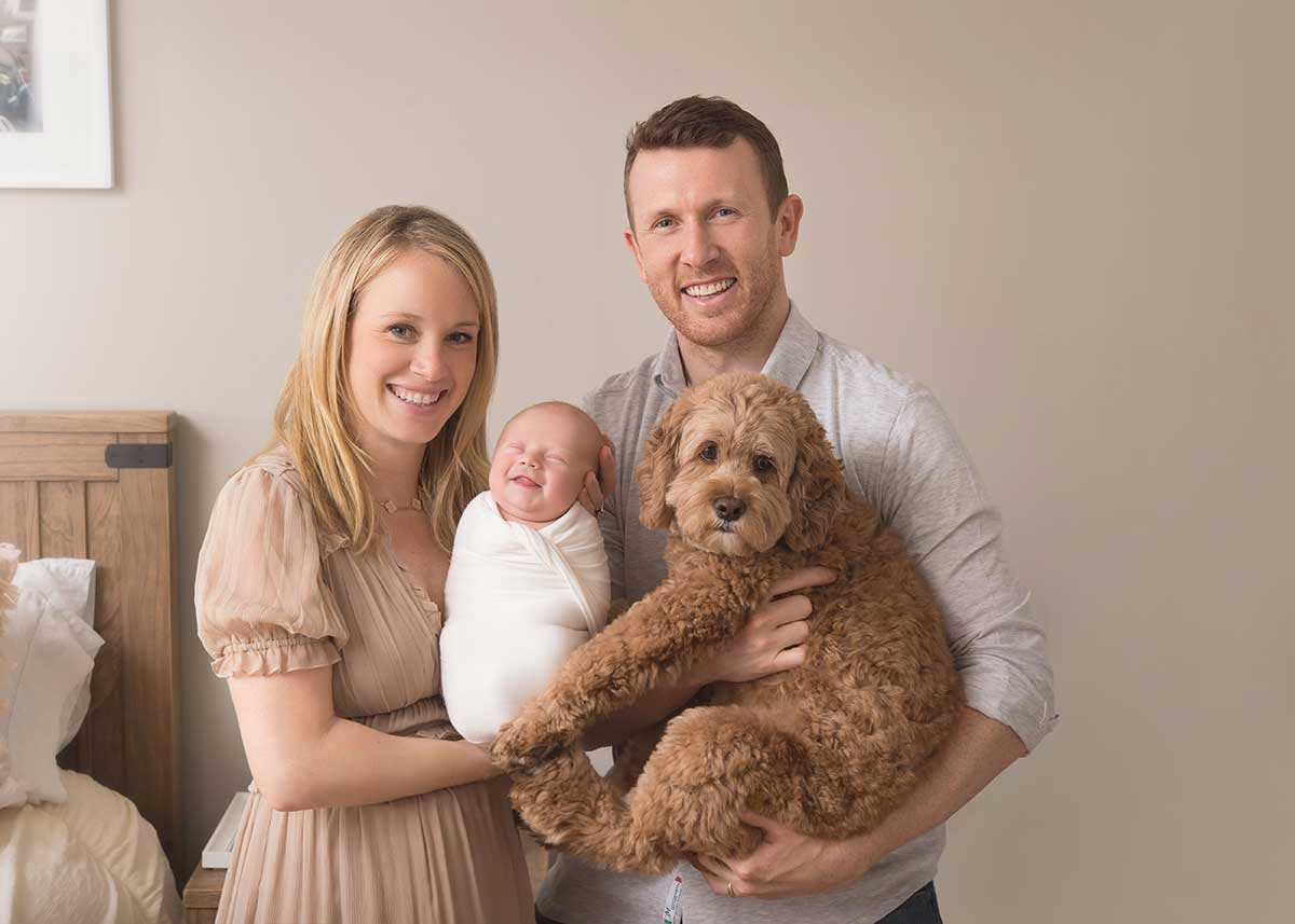 Cute smiling newborn baby in a family photo