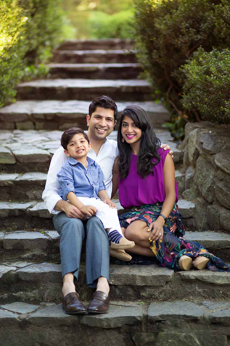 Family photo of a mother, father and their son on a beautiful stone path
