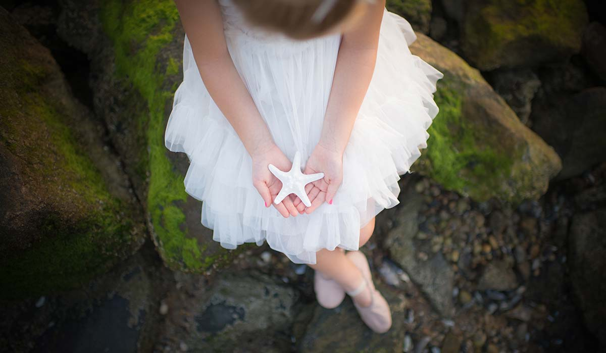 Girl in a white tutu holding a starfish