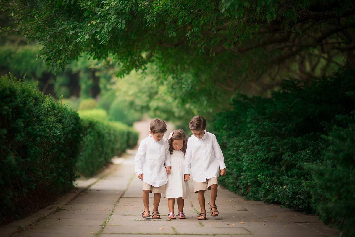 Three children walking on a paved path in botanical gardens near Scarsdale, NY