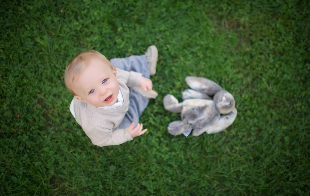 A boy and his stuffed toy are enjoying an afternoon in a park