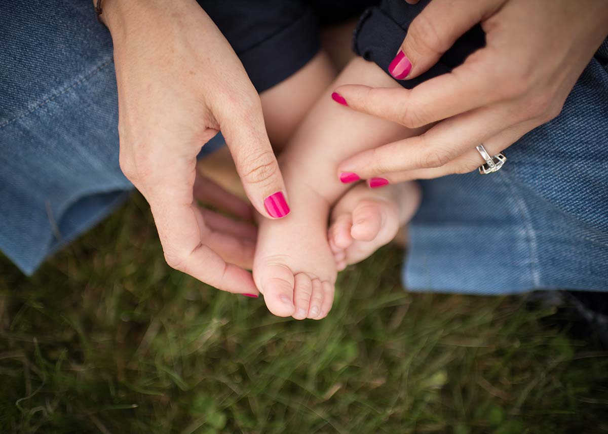 Closeup photo of a mother holding her baby's feet in the park
