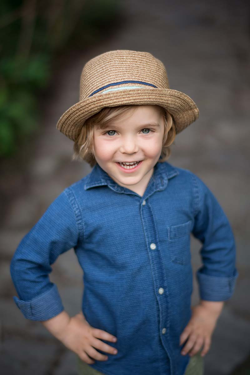 Handsome boy with blonde hair, blue shirt and a fedora hat smiling happily at the baby photographer.