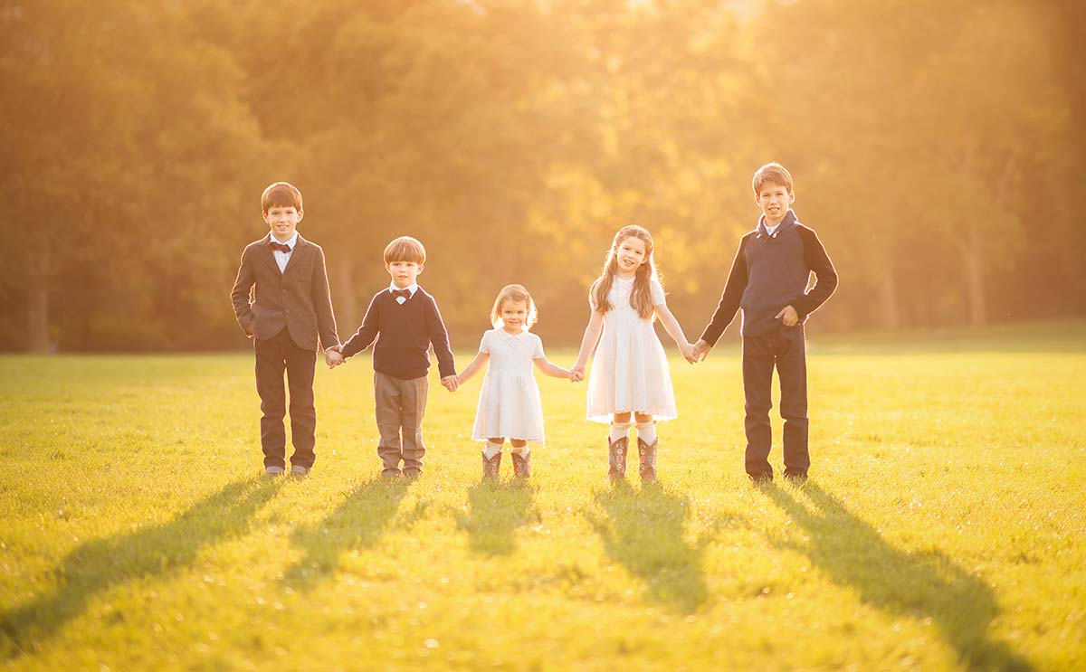 Five little children holding hands during a sunset at a beautiful setting at a park in Westchester County, New York.