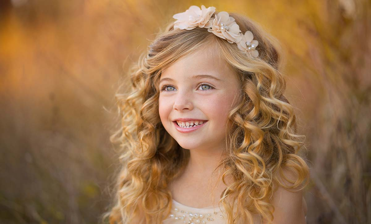 Beautiful young girl with curly blonde hair and a headband smiling