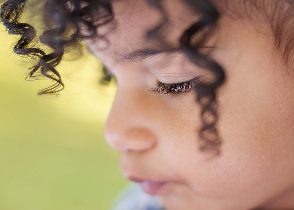 Closeup of eyelashes on young girl with black curly hair
