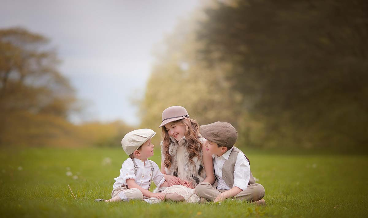 Three beautiful children wearing hats and stylish clothes smiling together in a grass field in Greenwich CT.