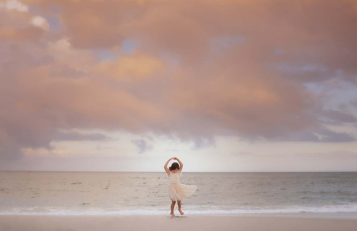 Timeless photo of a girl in a tutu skirt dancing on a beach in Stamford CT.