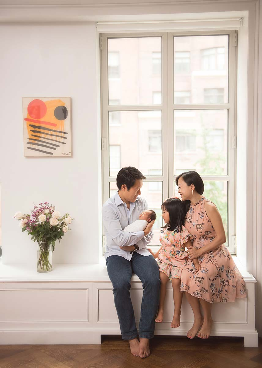 Lifestyle moment between parents and their children in this newborn themed photo
