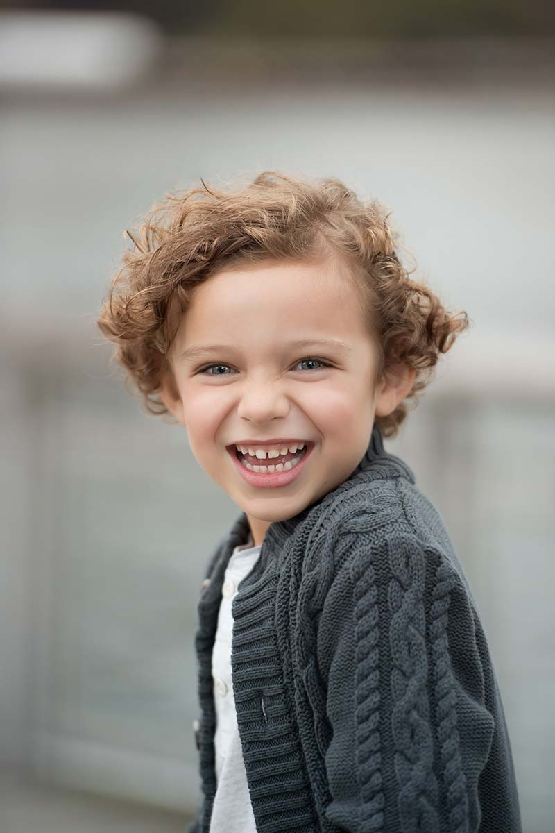 Handsome young boy smiling during a baby photoshoot in Connecticut.