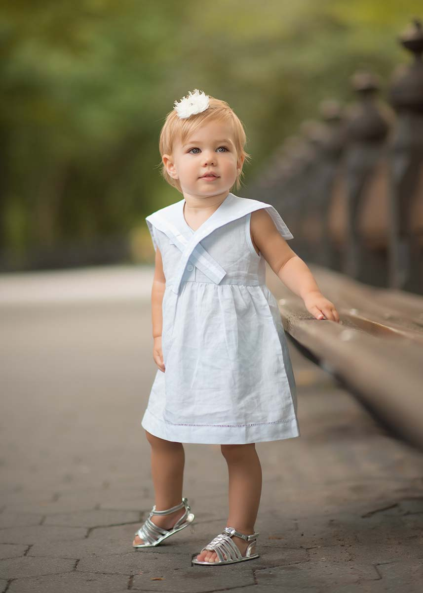 Pretty little girl wearing a dress and holding onto a bench