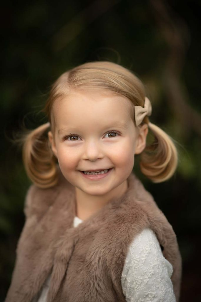Young blonde girl with pigtails smiling at the baby photographer